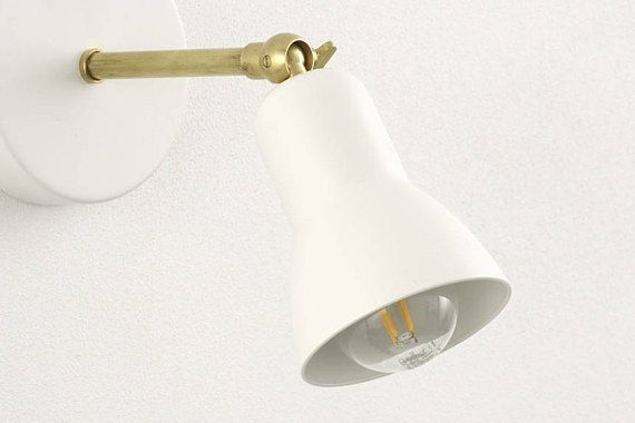 Brass wall sconce with white shade and knuckle joint