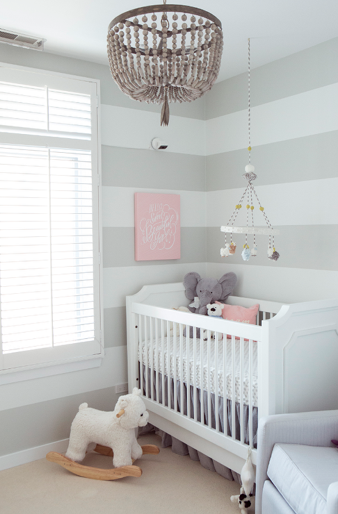 White And Gray Nursery Features Walls Painted With Stripes Lined A French Crib Pb Kids Ava Regency Dressed In Ruffled