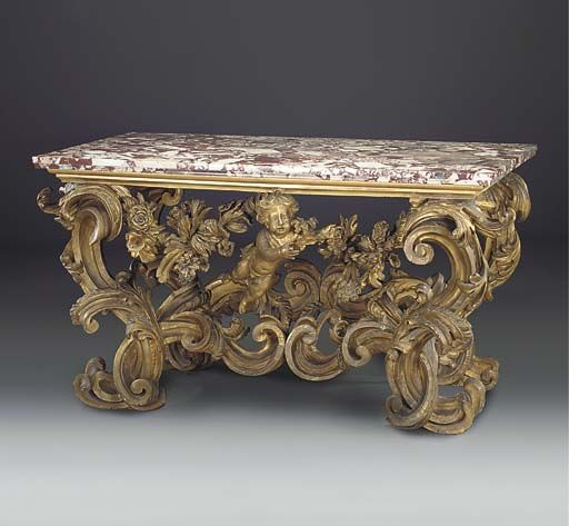 A ROMAN GILTWOOD CONSOLE TABLE, EARLY 18TH C. With a later red variegated marble top, on interlaced scrolled foliate supports, hung with floral and foliate swags and centred by a putto, 37in. (94cm.) high, 66in. (168cm.) wide, 32½in. (83cm.) deep