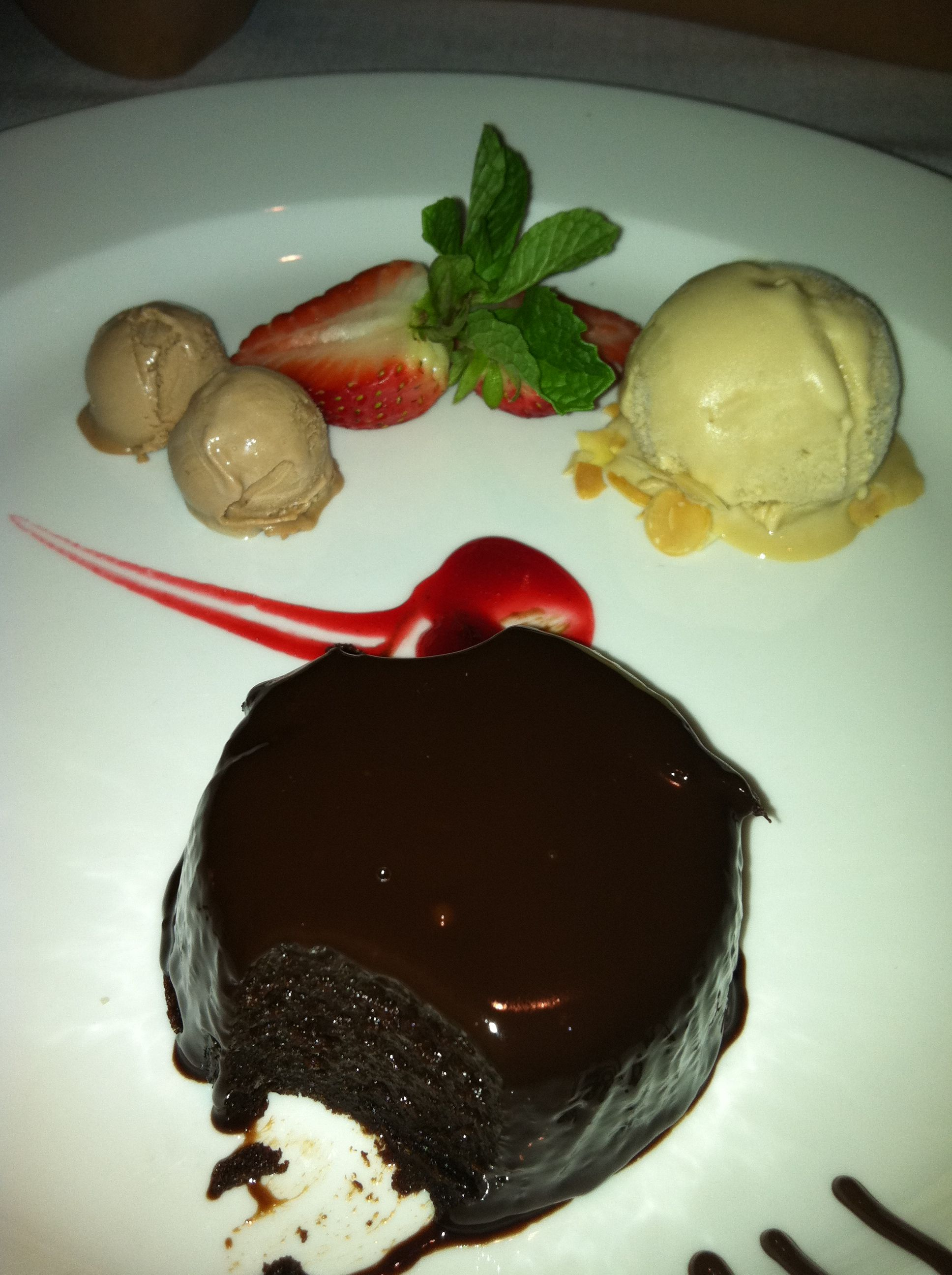 Warm chocolate cake with almond ice cream and berry sauce