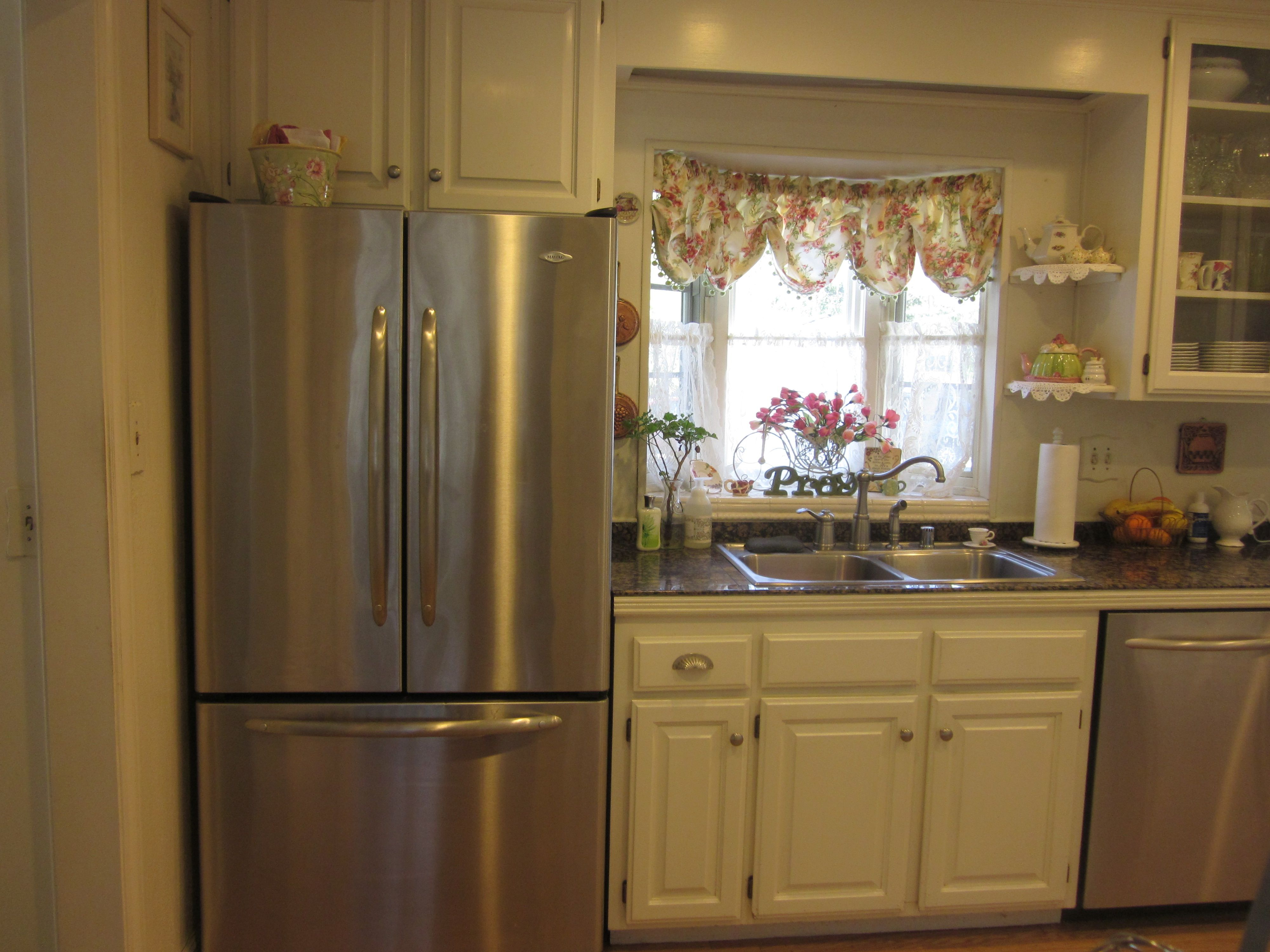 A Maytag french door refrigerator in stainless steel is against the
