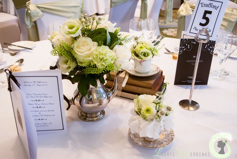 Table decoration with flowers in vintage teapots