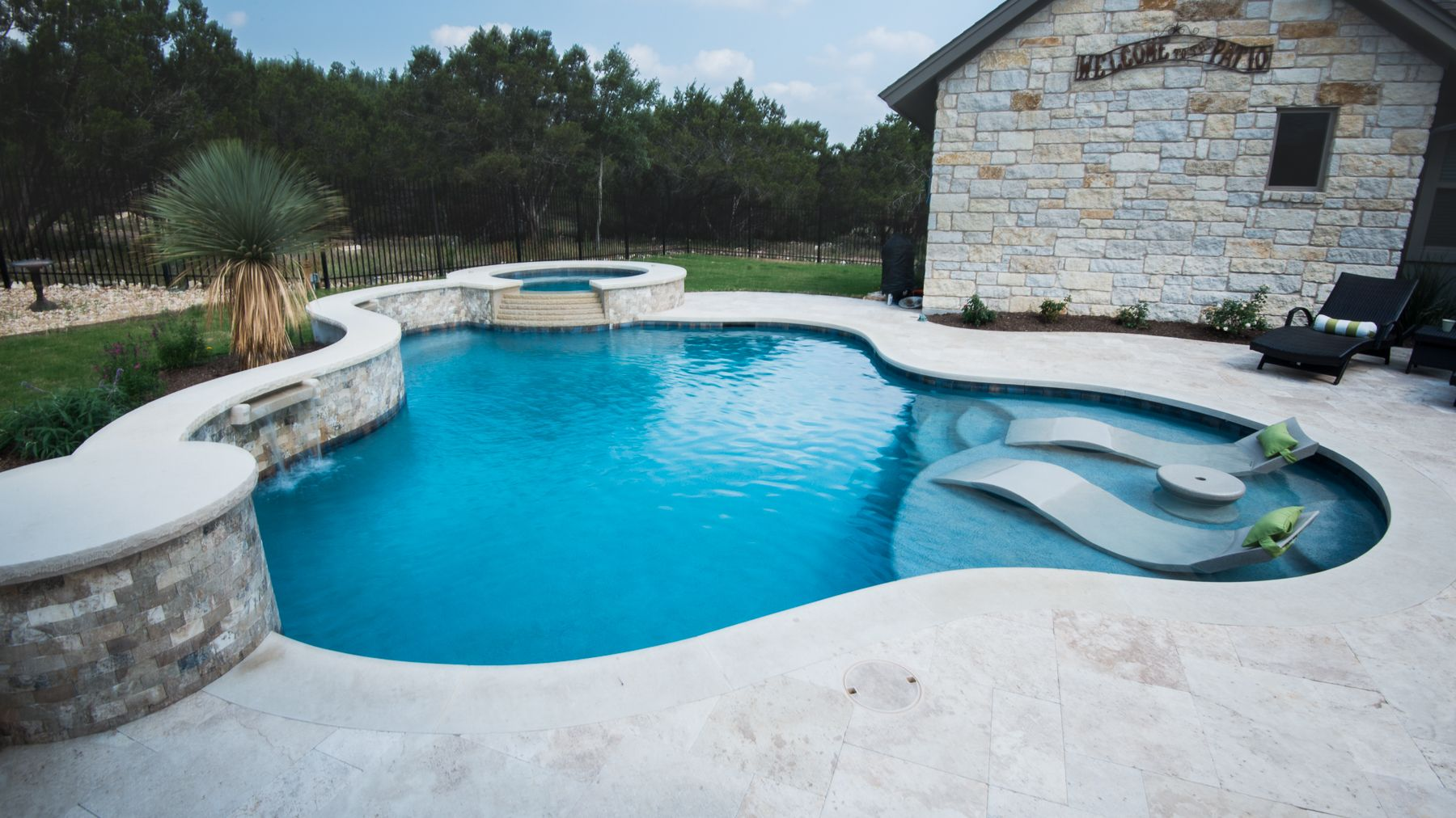 Freeform Pool With Ledge Loungers And Travertine Decking In Texas