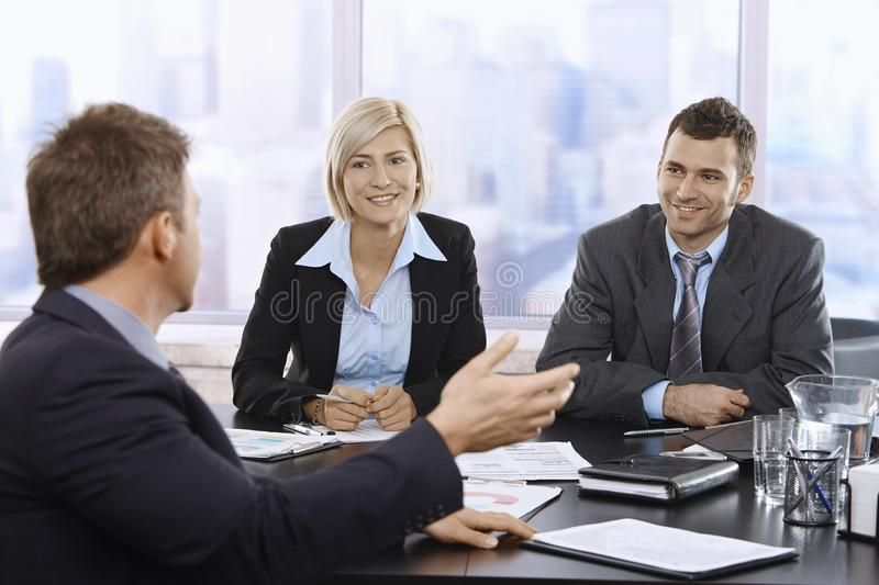 Business Meeting In Skyscraper Office With Smiling Mid Adult