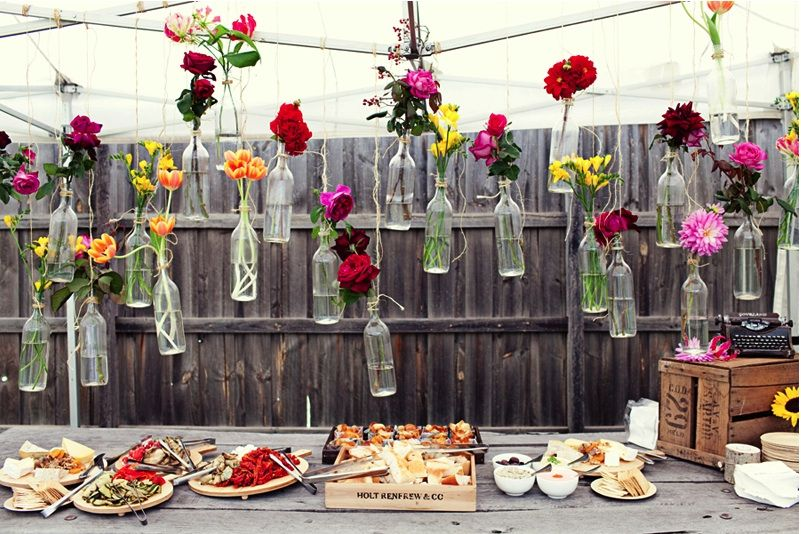 A Pretty Backyard Surprise Wedding The Sweetest Occasion Bottle Centerpieces Picnic Wedding Hanging Flowers