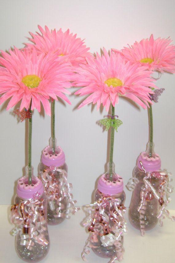 centro de mesa con flores y chupete para baby shower