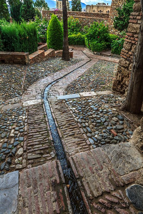 Water rill comes from Puerta de Los Cuartos in the Alcazaba of Málaga in Malaga, Spain  Water rills are used to flood beds or water trees in orchards  They still act as canals to bring water into the is part of Outdoor gardens landscaping -