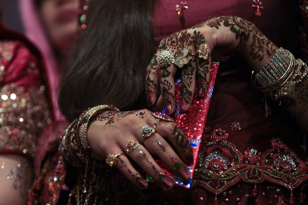 A girl shows her decorated hands during a bridal competition show in ...