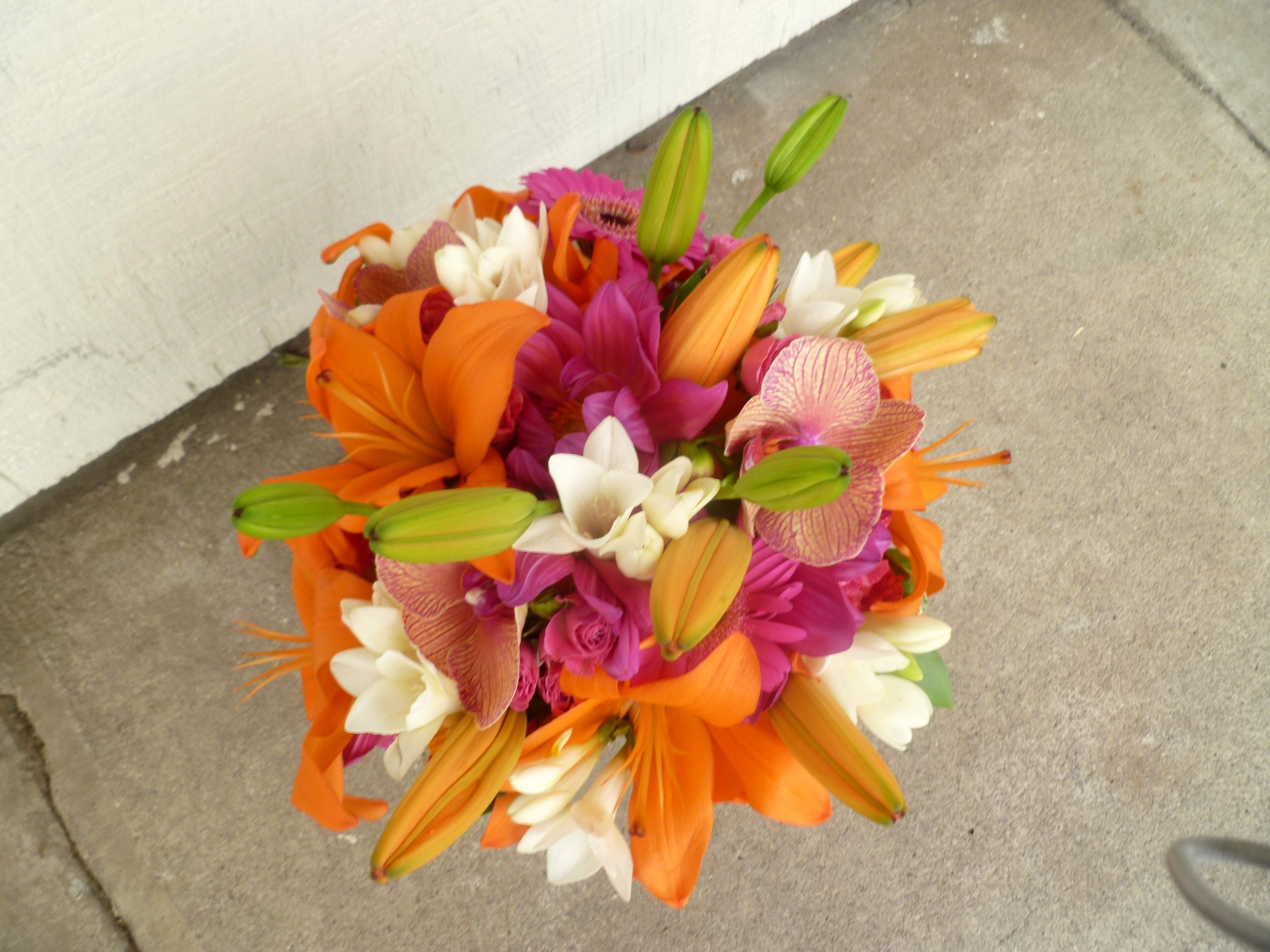 Orange asiatic lilies and orange roses are accented with pink and white