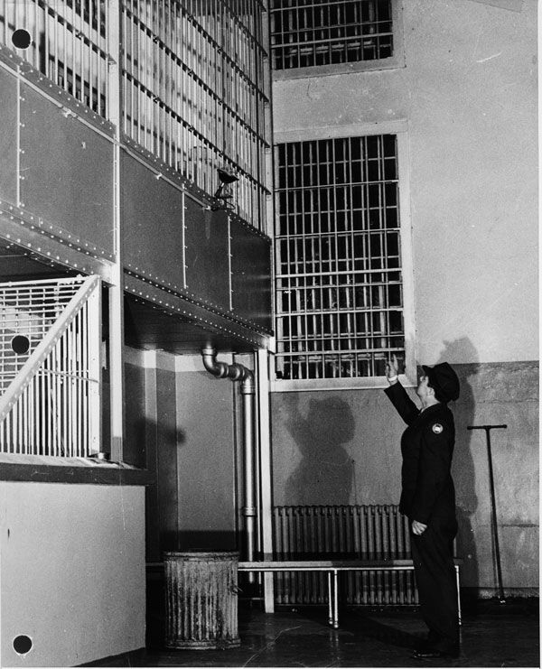 Correctional Officer Pointing To The PriedOpen Bars A