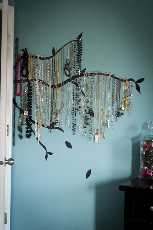I may put my own twist on this (instead of nails and painted branches) and buy or create flat metal branches and hinge them onto the wall by the mirror so they swing out for easy access.