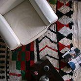 モロッコのAZILALラグです。 AZILAL(アジラル)というのはモロッコの地名です。モロッコでは作られた地名がそのまま名前として使われているようです。AZILALよりも目の詰まったBENI OUARAIN(ベニワレン)も有名ですが、これも地名がそのまま名前になっています。 このラグは幾何学的な模様と鮮やかな赤と緑のカラーが特徴です。茶色の幾何学、赤と緑、赤と黒の幾何学と3つのエリアに分かれているような柄なので、見せ方もいろいろ楽しめそうです。クリスマスに使ってみても面白いかもしれませんね。幅も150cmあるので、広々としたお部屋でも活躍してくれそうです。手作りのため両端の幅が若干違いますが、それも手作りならではの面白さだと思います。     良質のウールを用いて一つ一つ手で織られている為、全て世界で一つしかない柄になっています。モロッコでも冬は非常に寒くなる山岳地帯の生活必需品として作られているので非常に丈夫で冬場をしのぐのに十分な暖かさを保ってくれます。手触りも柔らかく品質の高さがみられます。
