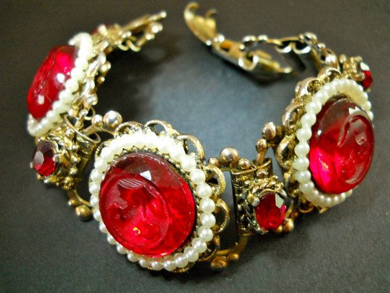 Offering a red Victorian Revival bracelet with glass-carved flowers in a book chain backing. There are 3 round glass panels which have raised
