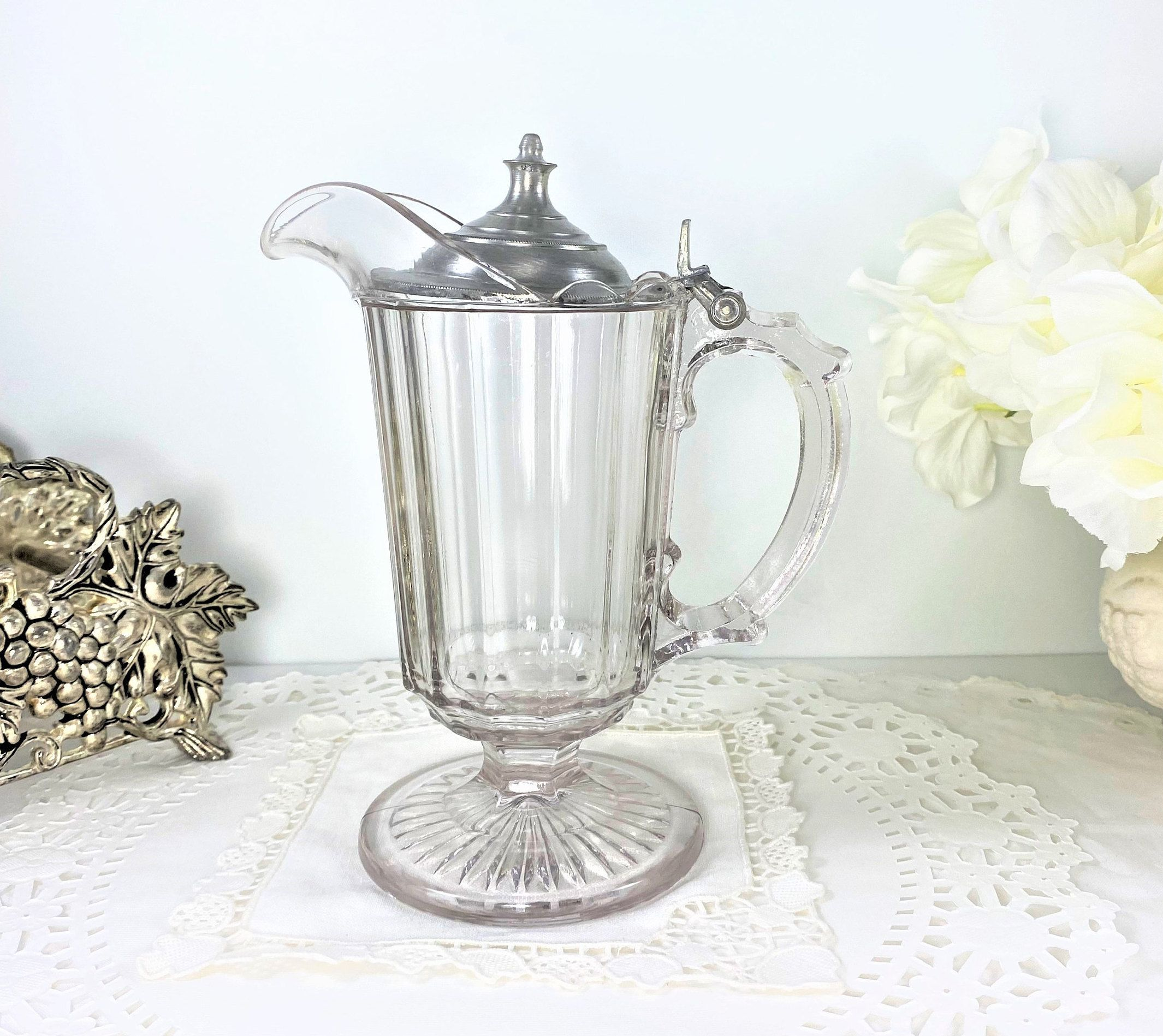 """This is a beautiful heavy pressed glass footed pitcher with an ornate handle and hinged lid. It measures 7 1/4"""" high to tip of lid, and approximately 6"""" wide from spout to handle. Its weight alone is 1 lb, 5.4 ounces. Holds 8 fluid oz. comfortably! in very good vintage condition!  NO nicks, chips, cracks, repairs. A wonderful pitcher that can be used for cream, syrup, etc. There are no makers marks to be found. Please examine pictures carefully as they are part of the description. Thanks for visiting Shoreline Vintage! To view our complete Etsy Shop, please go to: https://www.etsy.com/shop/ShorelineVintage"""