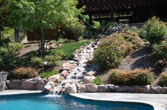 Gorgeous waterfall flowing into a swimming pool! What an awesome idea for your home.