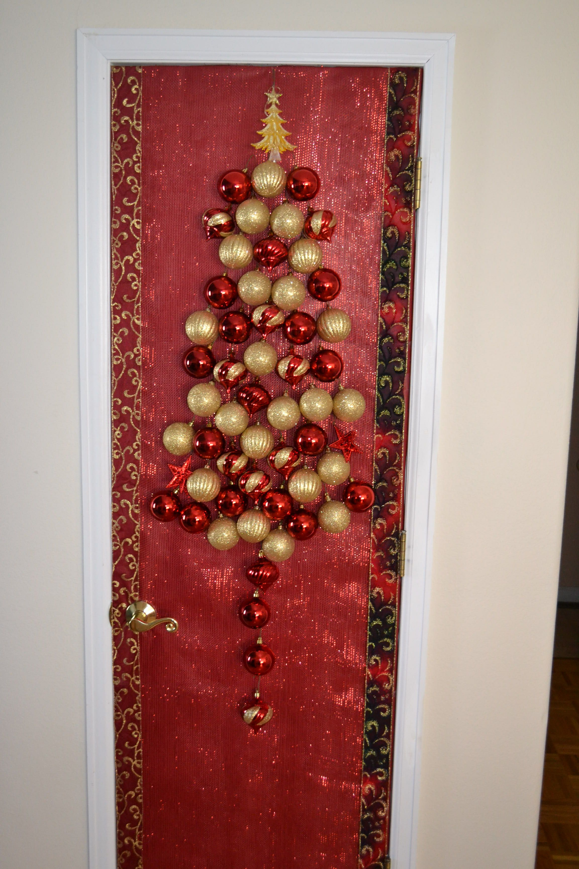 Take door off, wrap with paper, then staple xmas mesh to top & bottom. Hang ornaments from mesh with hooks & voila!