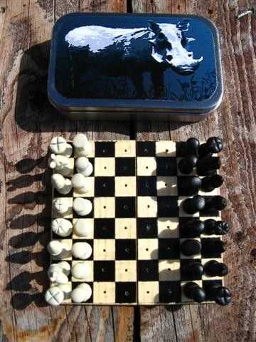 Mini Travel Chess in Altoids Tin. What a clever idea!  Folding wood board, pieces sculpted on push pins.
