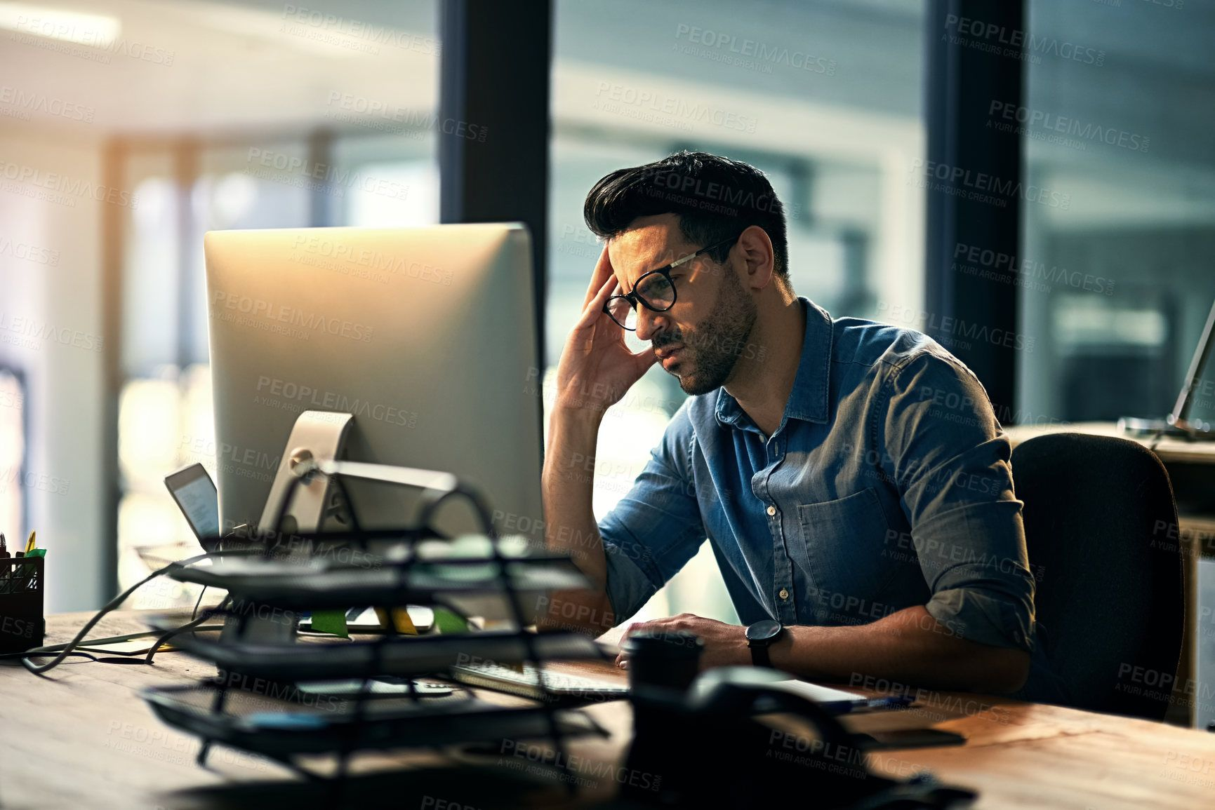 Shot Of A Young Businessman Experiencing Stress During A Late