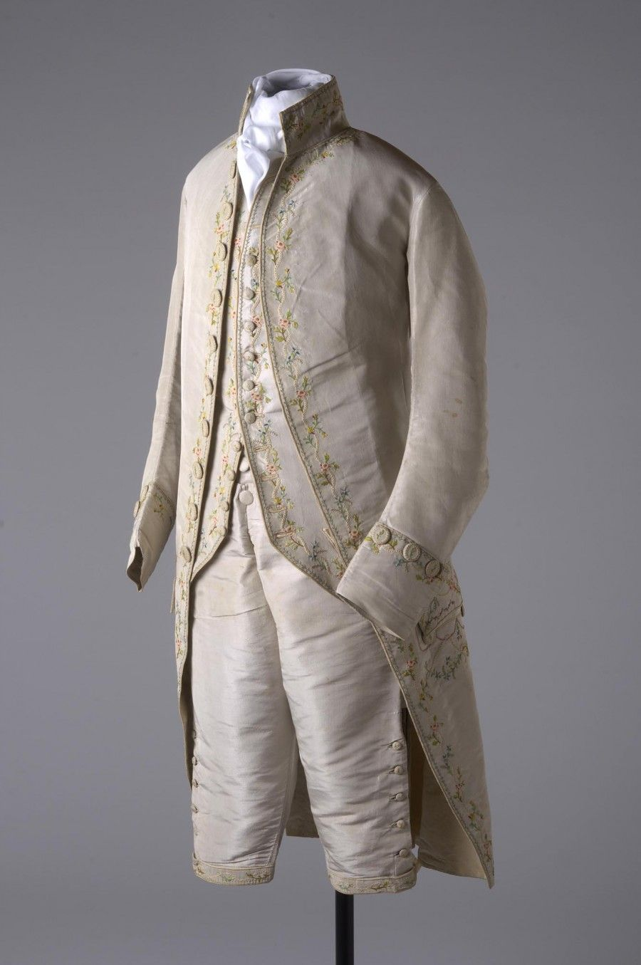 3-piece suit, Great Britain, 1780-1788. Grey silk, tambour embroidered on knee bands and buttons in pink, red, blue, yellow, green, brown and cream coloured silks, fronts lined with ivory silk in scrolling floral motifs.
