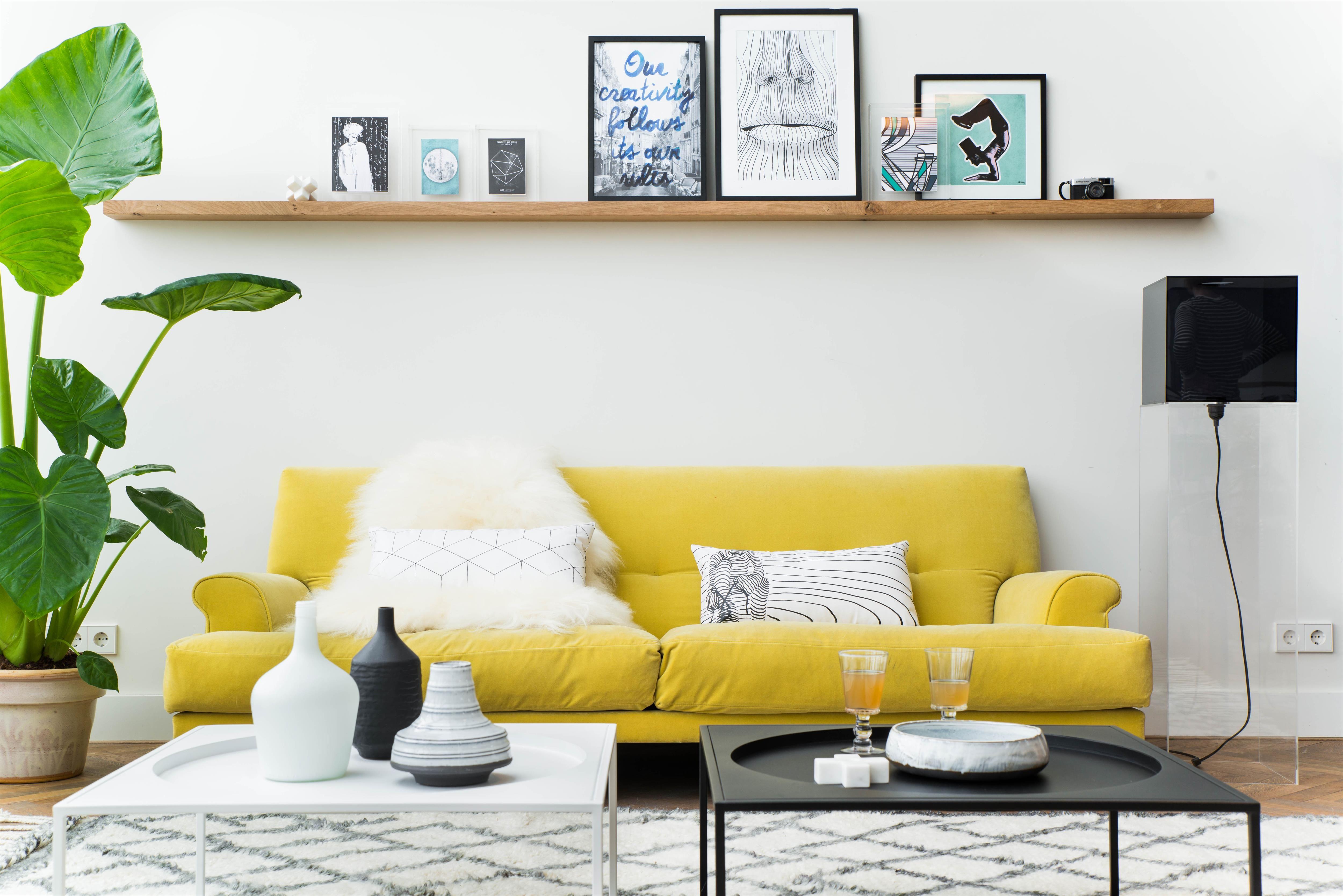 Mooi beeld van een woonkamer met een gele bank en vol meubels en ...