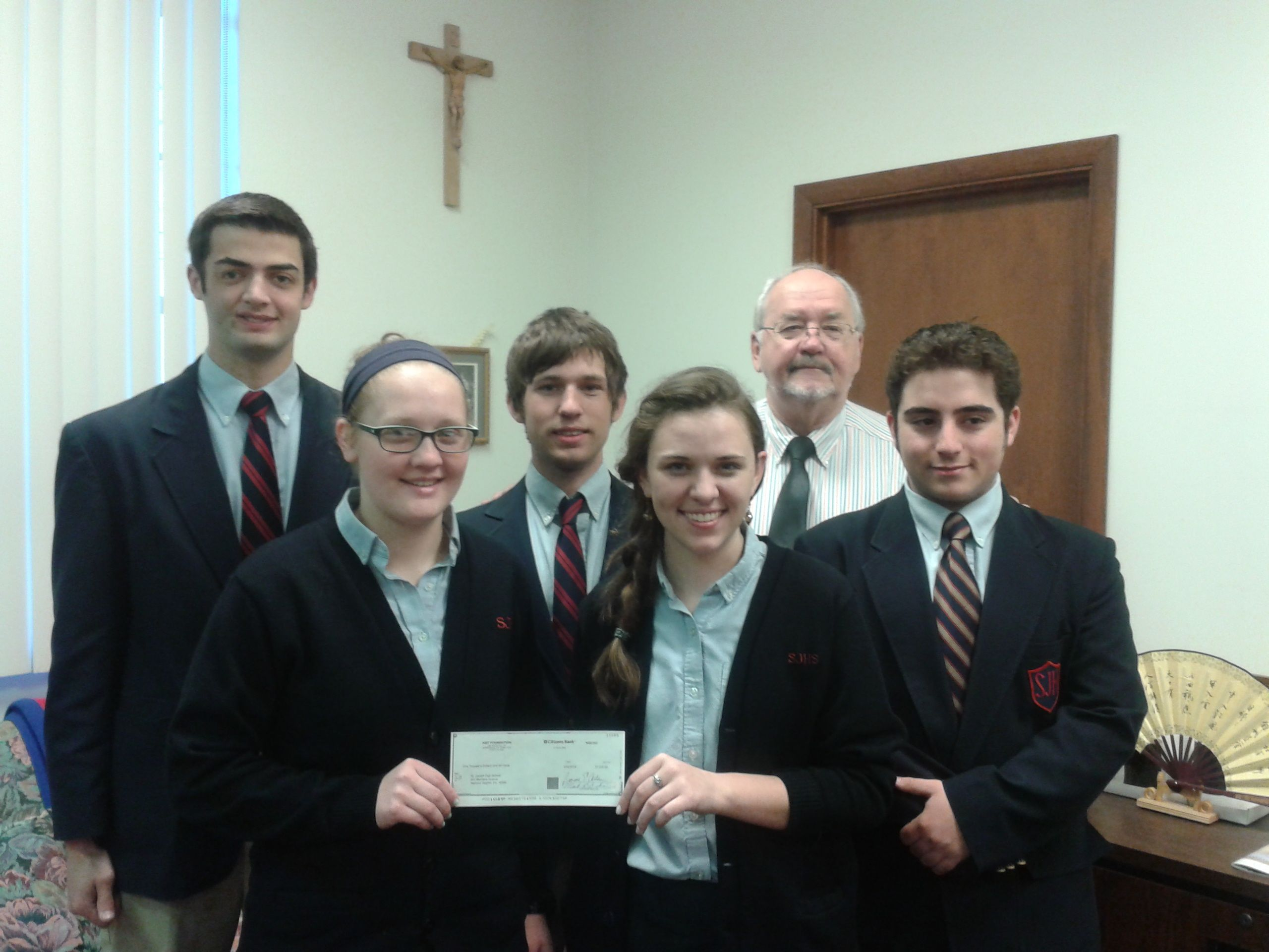 """This morning, the $1,000 prize check from AIST's """"The Real Steel"""" video contest was given to the principal from participating students and teacher Mr. Wes."""