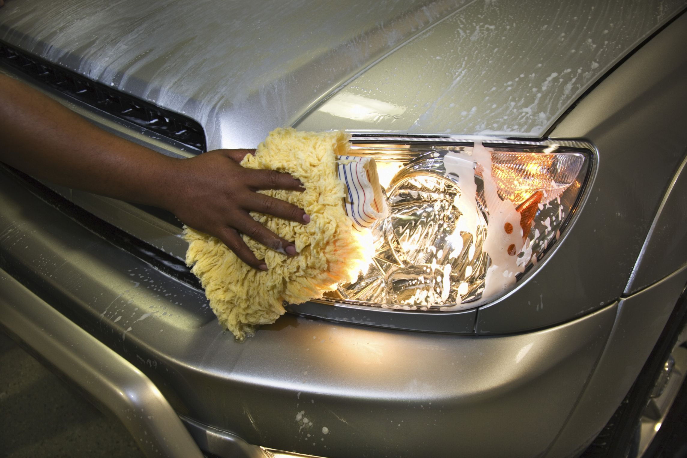 Closeup of hand cleaning headlight how to clean