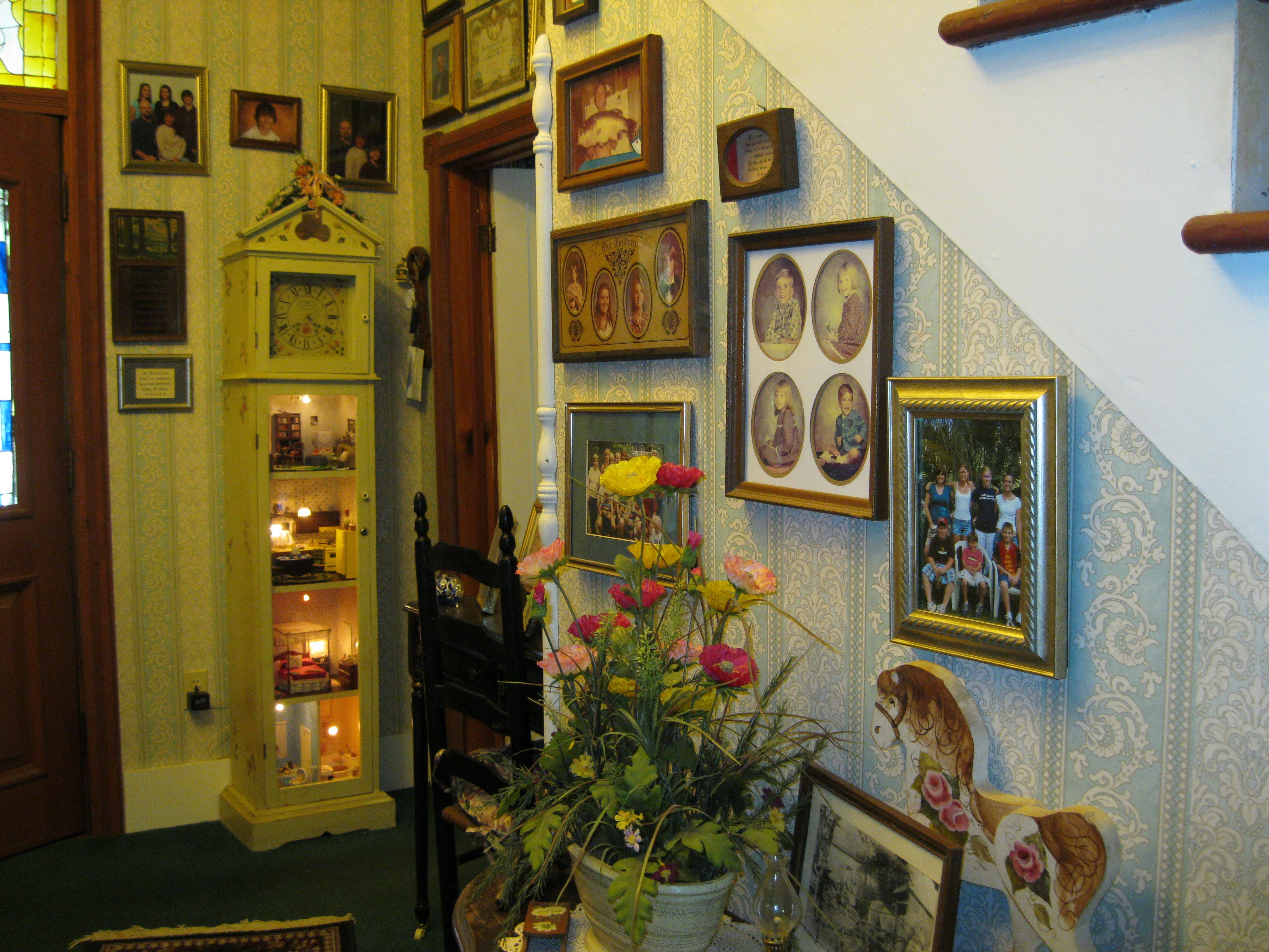 Our downstairs hall is our photo gallery. Lynn and I made the lighted grandfather's clock miniature house.