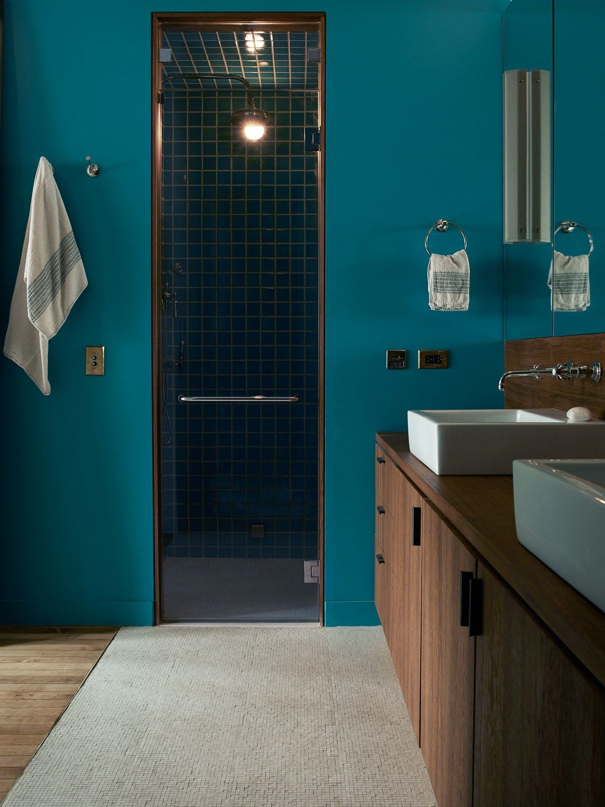 The master bathroom, swathed in Benjamin Moore's San Jose Blue,  features a steam shower wrapped in tiles by Heath Ceramics. The radiant heated floor is paved in limestone tiles in Stone Mosaic by Waterworks. The teak finished vanity, counter and backsplash are custom.