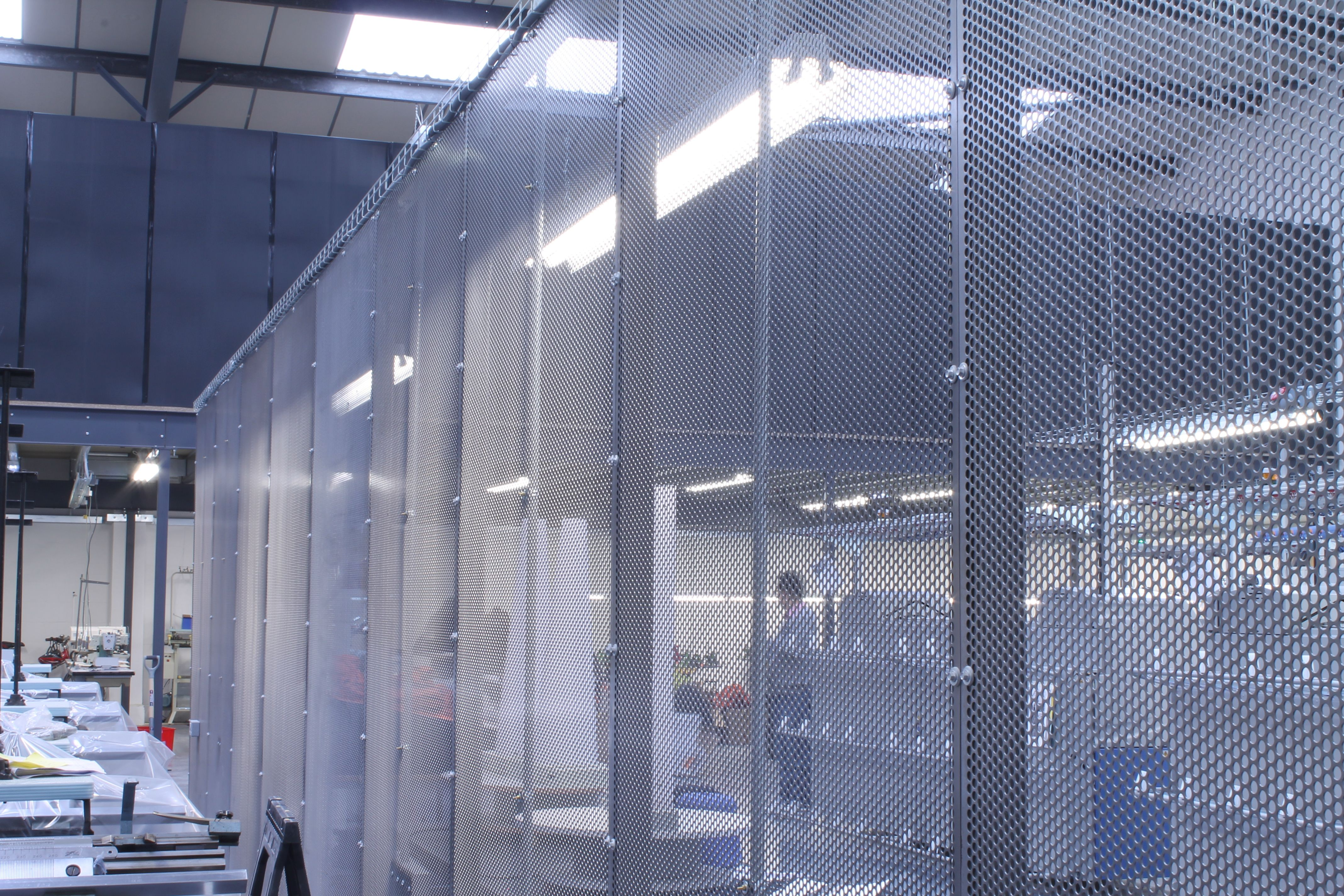 Wire Mesh Partitioning Wall Built For Both Employee Protection And Wiring To Hang Lighting On The Lower Factory Floor