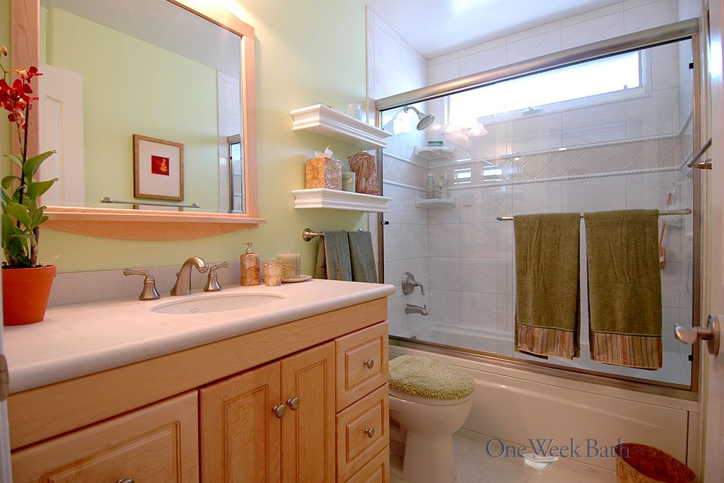 The traditional style bathroom with light wood and bold green walls was created by One Week Bath. This bathroom remodel includes bright green walls with a light wood vanity. This traditional remodel is ideal for those who prefer old-fashioned style. #OneWeekBath #Green #Bathroom #Remodel