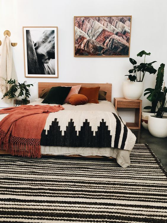 Bohemian Style Bedroom With Orange Accents And Striped Black White Rug