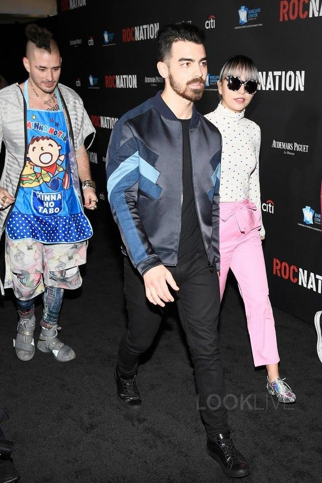 Joe Jonas wearing  J Brand Tyler Slim-Fit Jeans, Common Projects Black Original Achilles Sneakers, Neil Barrett Bomber Jacket
