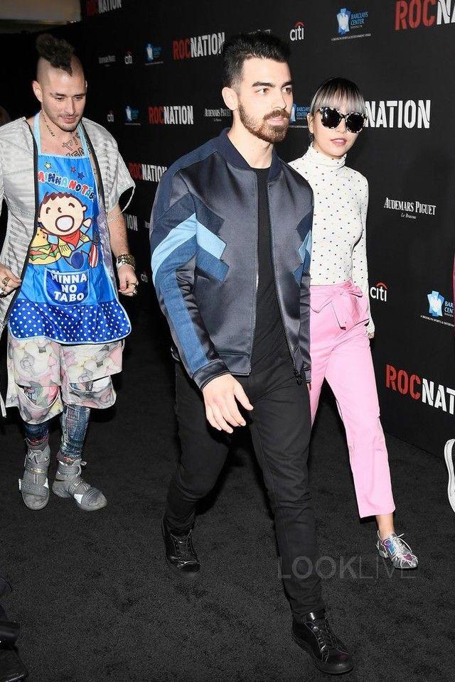 Joe Jonas wearing  J Brand Tyler Slim-Fit Jeans, Common Projects Black Original Achilles Sneakers, Neil Barrett Bomber Jacket
