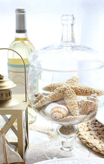 Decorate with seashells, sand and other beach elements in glass jars to keeps things clean