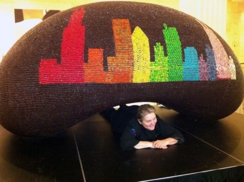 "Gloria Hafer, Culinary Arts Instructor for Chicago's After School Matters, poses under the giant chocolate ""bean"" sculpture covered in Jelly Belly(R) jelly beans and Jelly Bean Chocolate Dips(R) now on display at Jelly Belly Visitor Center in Wisconsin. The candy creation is a replica of Chicago's ""Cloud Gate"" by sculptor Anish Kapoor, which sits in Millennium Park. Photo credit: Jelly Belly Candy Company"