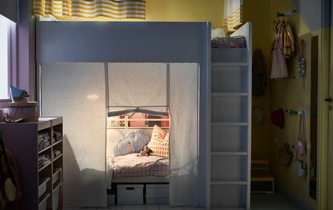 Et delt barnerom med loftseng og ei uttrekkbar seng under. Rundt hver av sengene er det hengt opp gardiner som skjermer mot innsyn