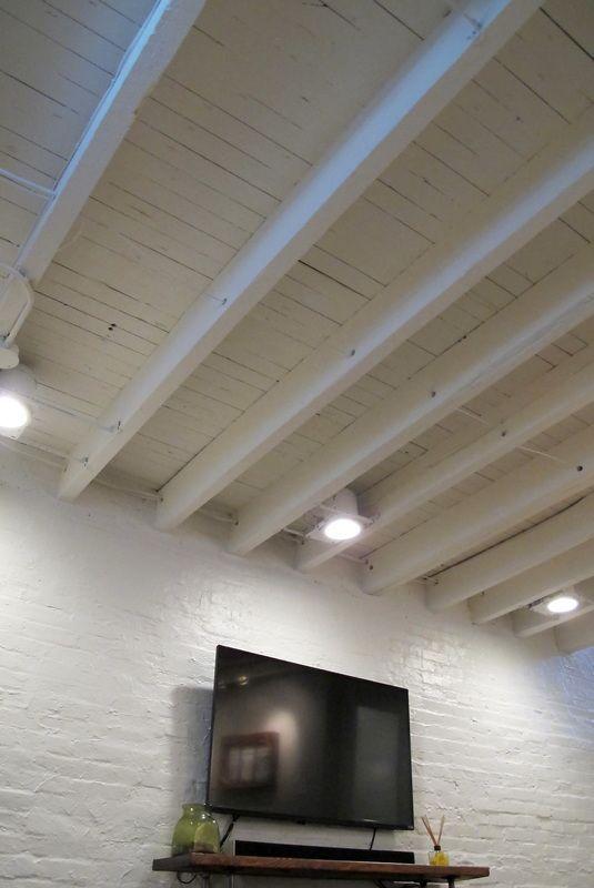Photo of Gemütlicher schicker Keller Reno mit herausgestellten gemalten Balken u. Hölzernen Fliesenböden