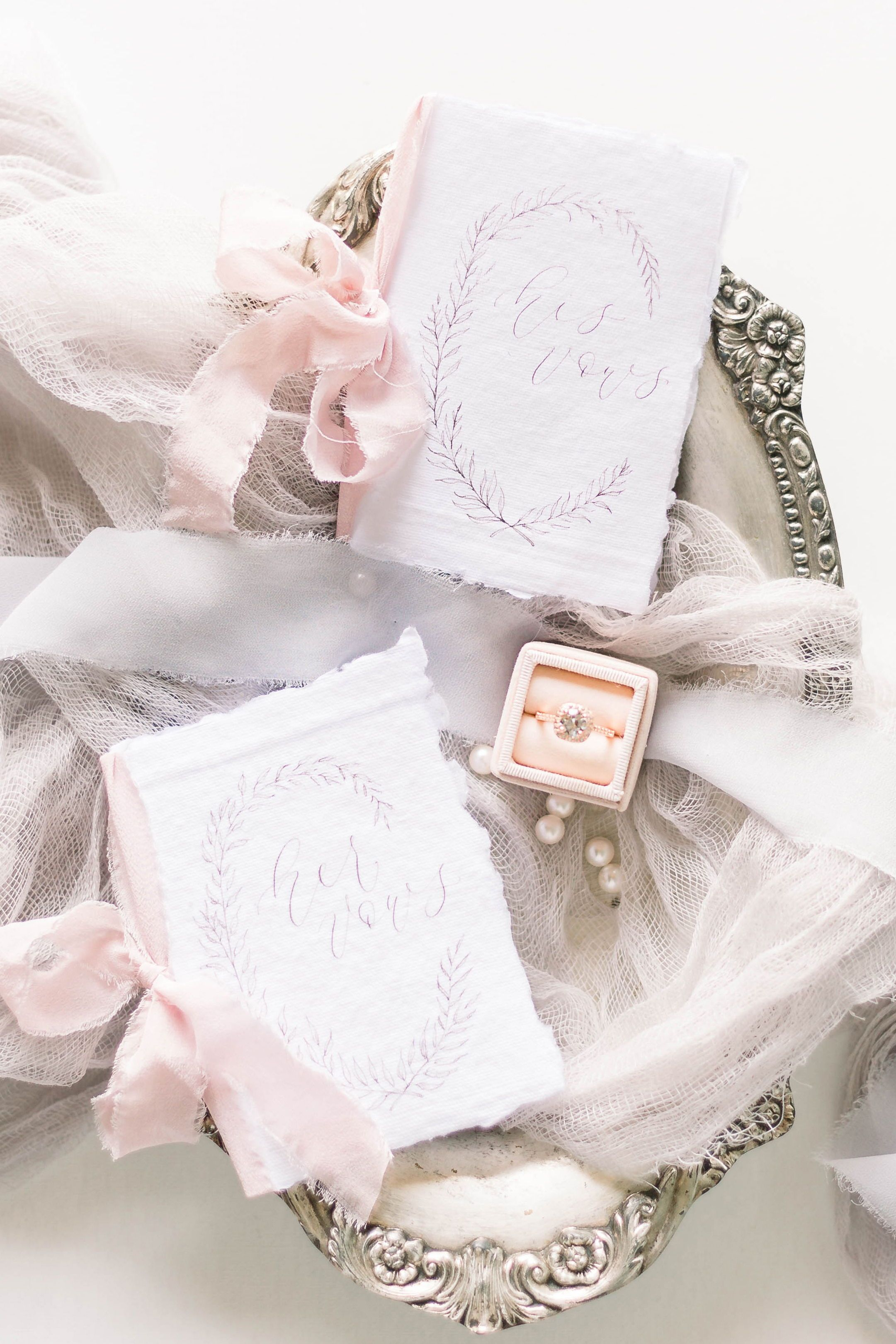Photo of His and Hers Vow Books Set with Handmade Paper Covers and Laurel Wreath Illustration.