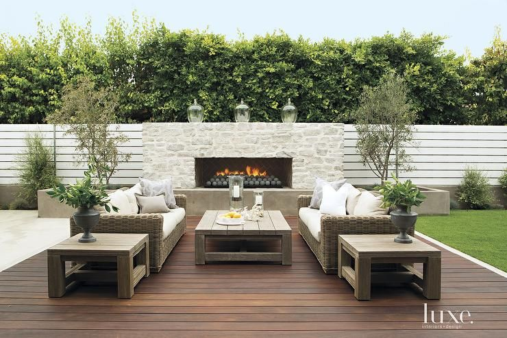 chic patio features a pair of wicker sofas facing each other across from a weathered teak coffee. Black Bedroom Furniture Sets. Home Design Ideas