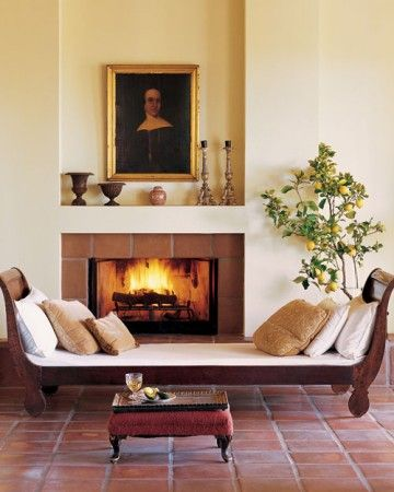 The hearth, baseboard, and floor are tiled with matching Mexican terra-cotta. The tiles' shapes set off the varied contours of a shiplike Empire daybed, the urns and candlesticks on the mantel, and the portrait of a woman above.