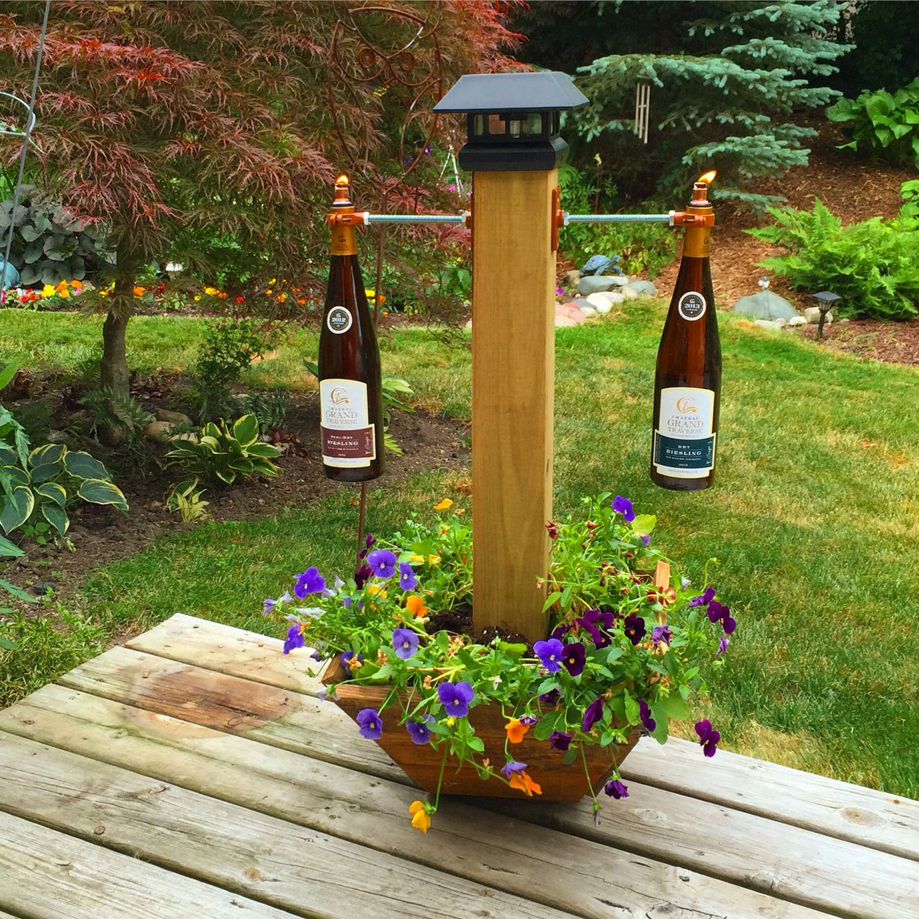 Dual tiki torch holder with a solar light on top and ...