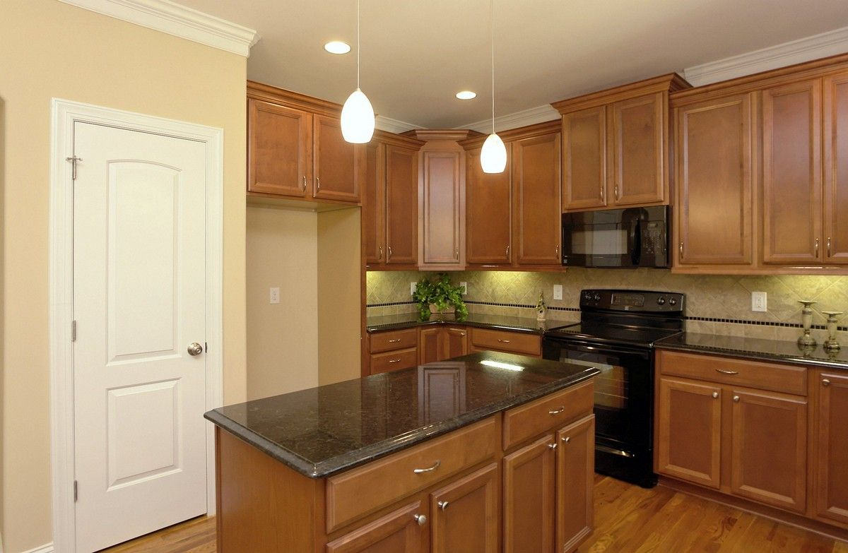 Island kitchen with black granite counter tops. Medium ...