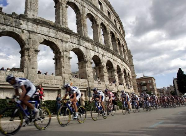 The Giro peloton races past an old Roman amphitheater in the northern Croatian Adriatic town of Pula.