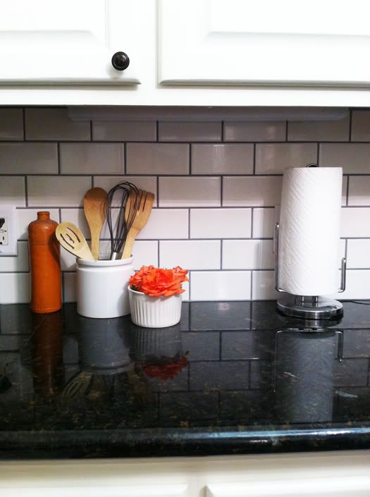 we love this classic kitchen backsplash using white subway tile and dark gray grout - How To Grout Tile Backsplash
