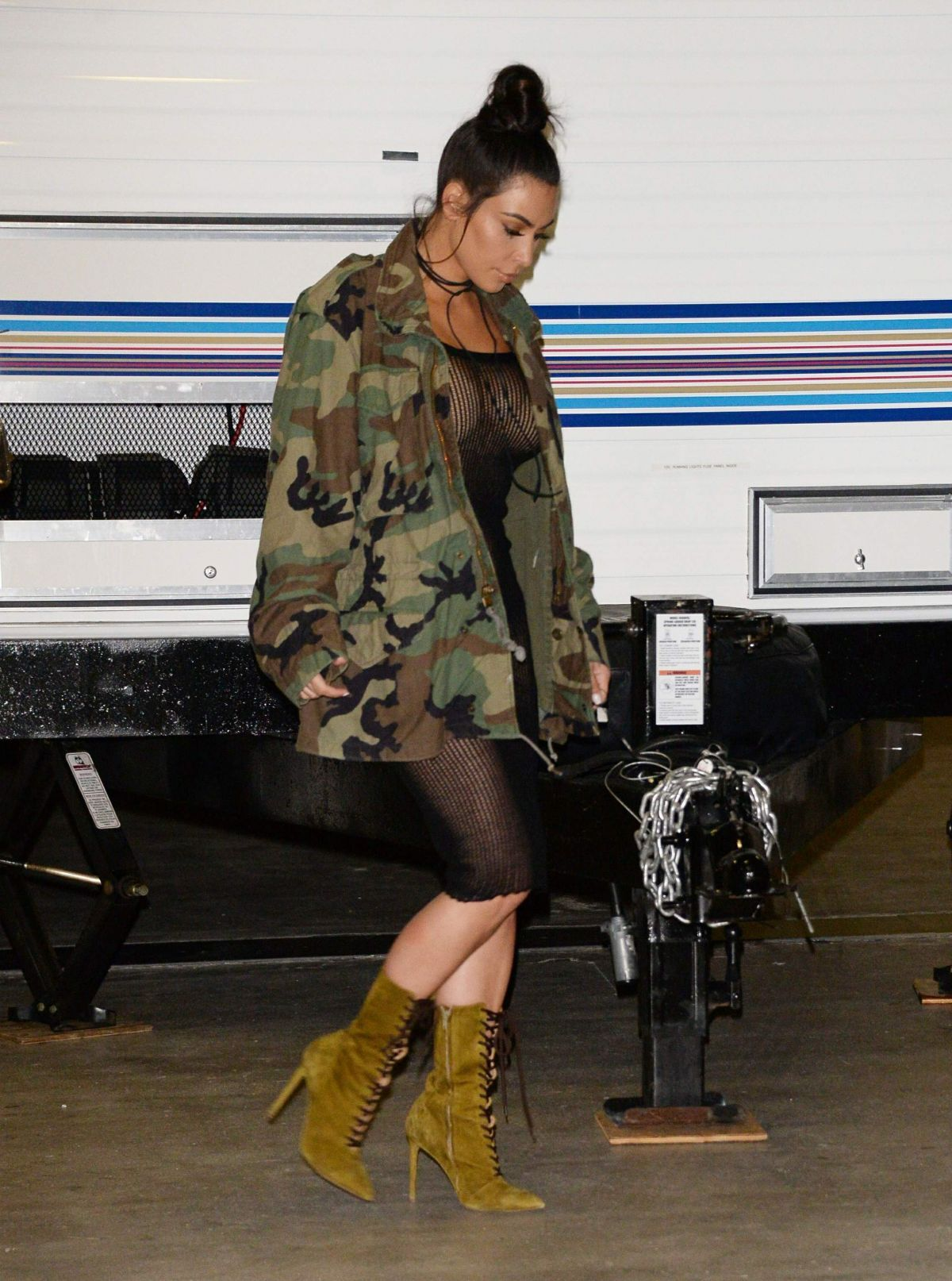 Kim Kardashian arrived at a party in L. sporting a Life of Pablo oversized  camo jacket and Yeezy Season 3 green suede lace up boots.