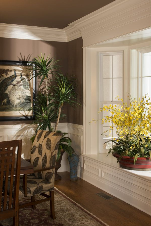 Dining room with large crown molding paneling to chair rail height and a deep window sill for Chair rail height in living room
