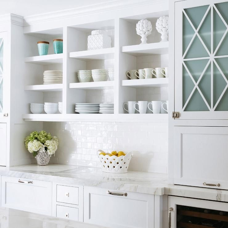 Bon White Kitchen Features Open Shelving Filled With Pottery Over A A White  Subway Tiled Backsplash And White