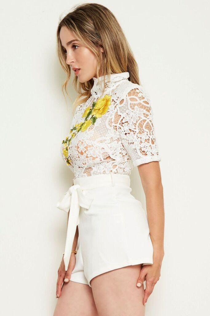 e01b68b46b59 This high neck lace romper is adorned with a rose embroidery patch and  features a waist tie with belt holes to cinch the waist and creates an  illusion of a ...