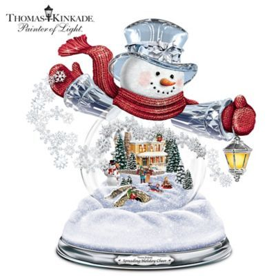 Handcrafted crystal glass snowman with a Thomas Kinkade-inspired scene within his swirling snow belly. Plays 8 favorite Christmas carols, lights up!
