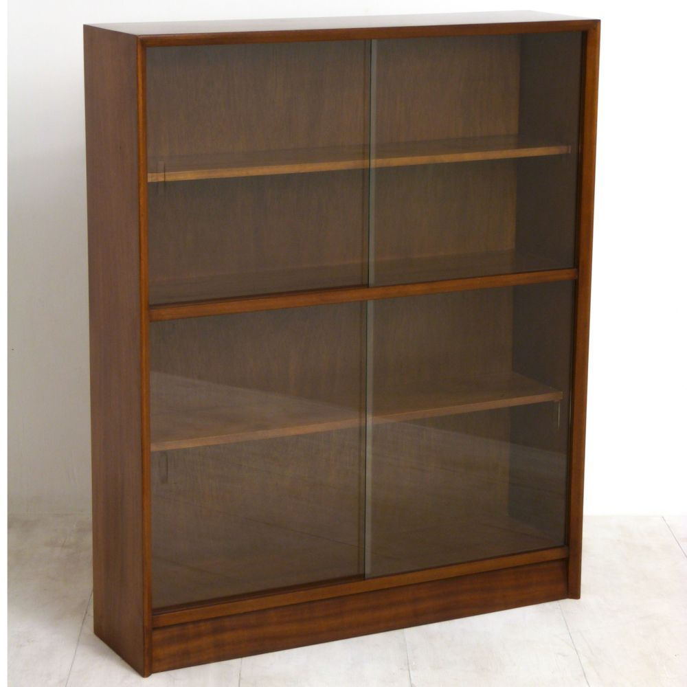 A Herbert E Gibbs vintage sliding glass door bookcase with two shelves.  Circa 1960. - A Herbert E Gibbs Vintage Sliding Glass Door Bookcase With Two